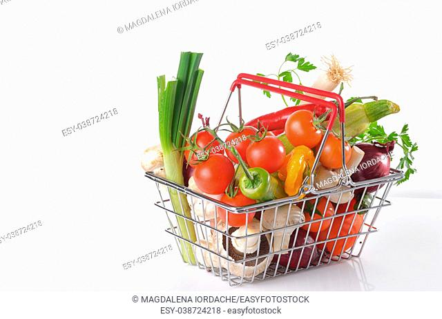 Raw vegetables in basket isolated on white