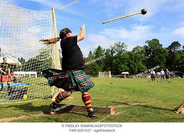 Competitor at Scottish highland games throwing the 22 pound hammer, a traditional Scottish competition taking place at Balloch near Loch Lomond, Glasgow