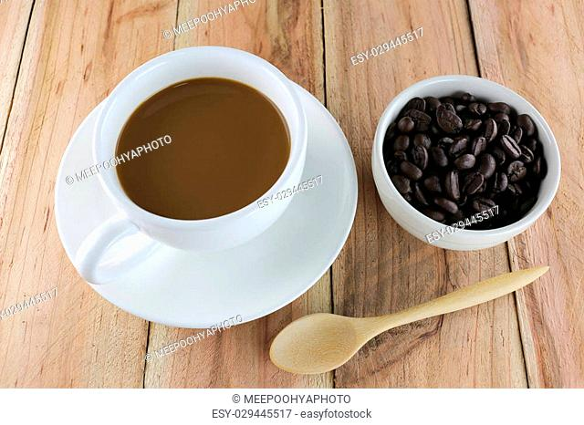 White coffee cup and wooden spoon on wood background