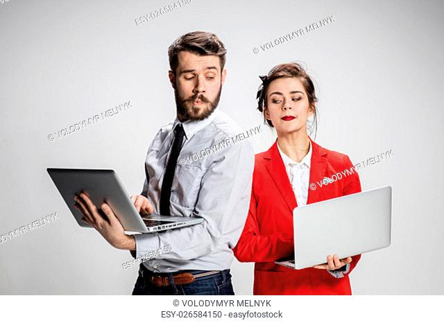 The young businessman and businesswoman with laptops communicating on gray background. The concept of relationship of colleagues