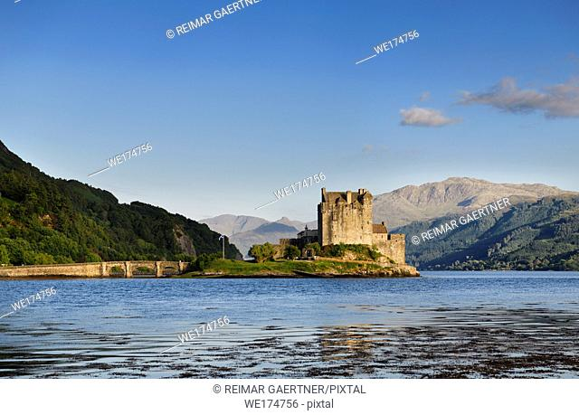 Restored Eilean Donan Castle on Eilean Donan Island with stone arch footbridge at sundown with Glenelg mountains Scottish Highlands Scotland