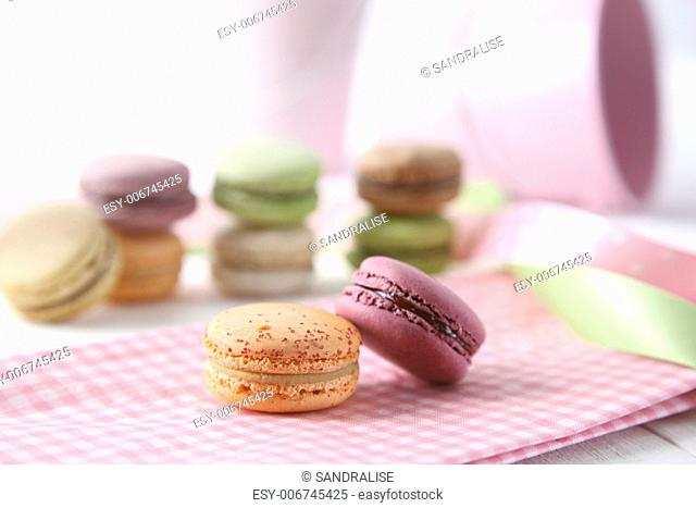 Macaroons with napkin on wooden table