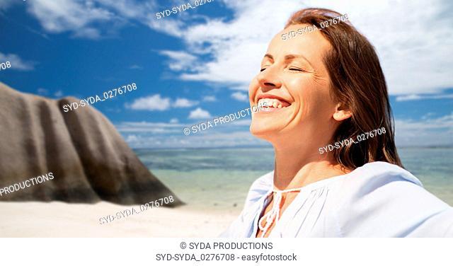happy woman over seychelles island tropical beach
