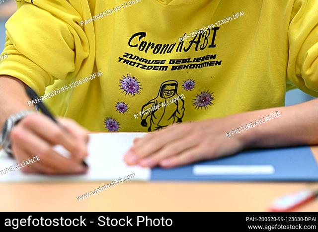 20 May 2020, Baden-Wuerttemberg, Ravensburg: A student writes during the German final examination in the gym of the Albert-Einstein-Gymnasium; on his hooded...