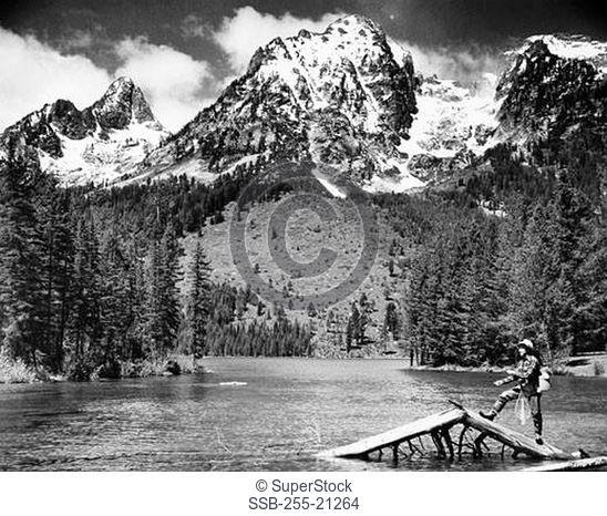 Fisherman standing on half submerged tree in a lake and fishing, Leigh Lake, Grand Teton National Park, Wyoming, USA
