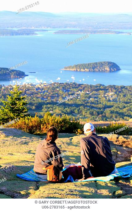 A couple sitting on a blanket enjoying the view of Bar Harbor from Cadillac Mountain Maine USA