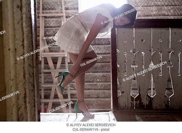 Young woman putting on heels at top of staircase