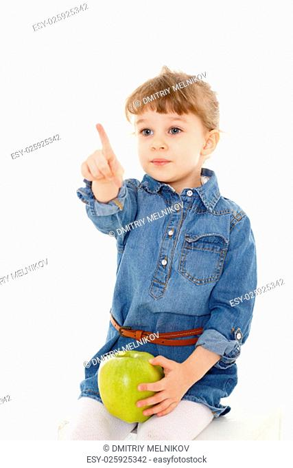 Sweet small girl with fresh big an apple sits on a white background. Healthy food. 3 year old