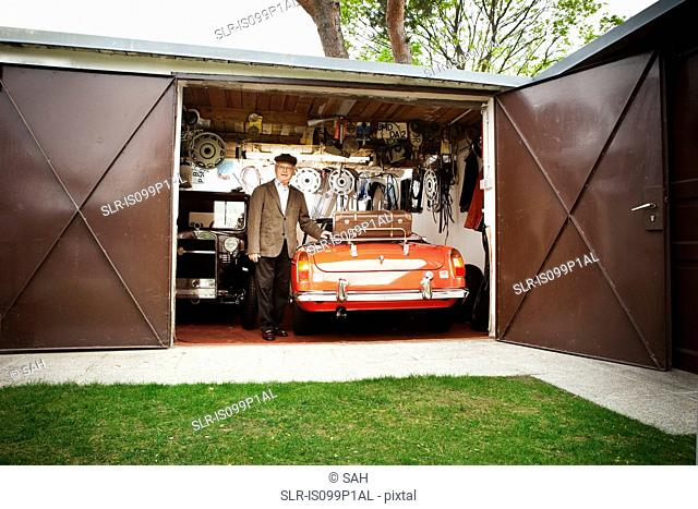 Senior man with vintage car in garage
