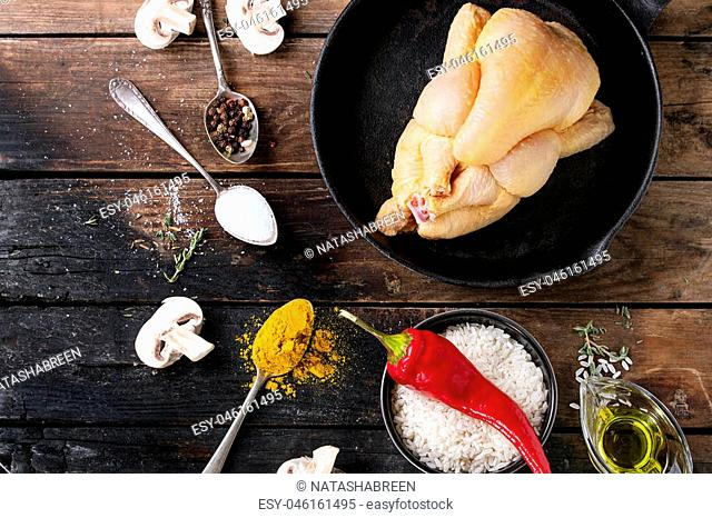 Whole raw mini chicken in iron cast pan with seasoning in vintage spoons, sliced mushrooms and bowl of uncooked white rice over old wooden background