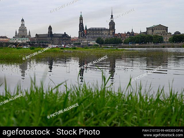20 July 2021, Saxony, Dresden: The water of the Elbe has slightly flooded the Elbe meadows on the bank in front of the Old Town with the Frauenkirche (l-r)