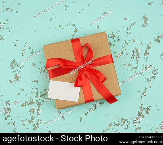 square box wrapped in brown kraft paper and tied with a red silk ribbon, on top of an empty white business card, green background