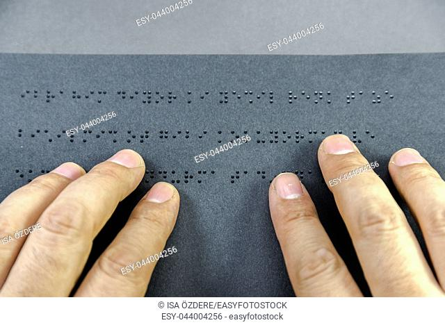 Top view of hand of a blind person reading a book written in braille alphabet for blind people. Copy space for editing. Istanbul,Turkey