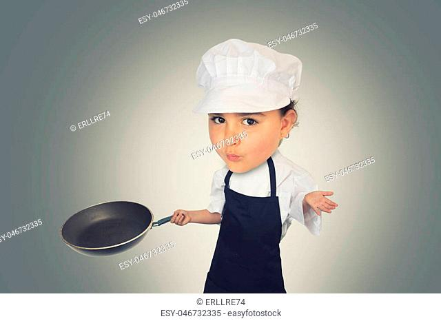 Portrait of a funny six years girl with a big head dressed like a chef on a grey background