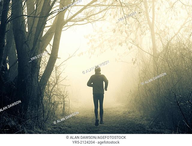 Man jogging in woodland park on a foggy day in winter. Billingham, north east England, United Kingdom