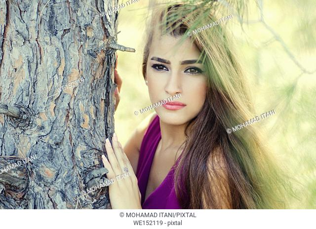 Beautiful young woman leaning against a tree looking away