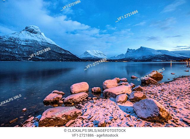 Blue sky at dusk and snowy peaks are reflected in the frozen sea Storfjorden Lapland Lyngen Alps Tromsø Norway Europe