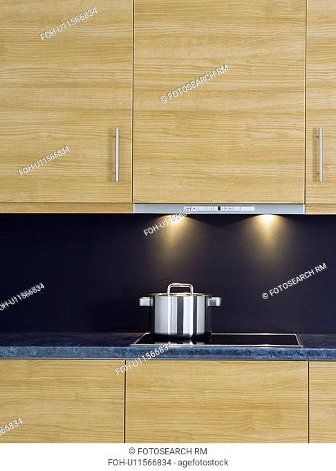 Close-up of stainless steel pan on hob below pale wood kitchen cupboard with concealed lighting&13,&10,&13,&10,&13,&10,&13,&10,&13,&10,&13,&10