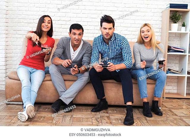 Two guys and two girls play on the game console. They are sitting on the couch and holding the joysticks
