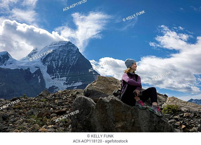 A young woman rests while at Hargreaves lake and glacier, off the Berg lake trail, with Mt. Robson in the background, Mt