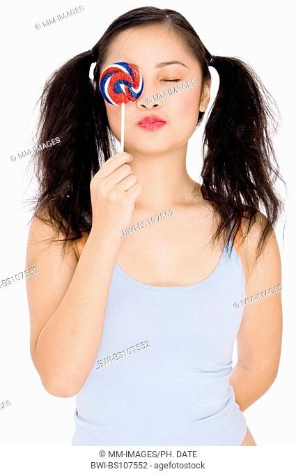 an asian teenage girl holding a colorful lollipop