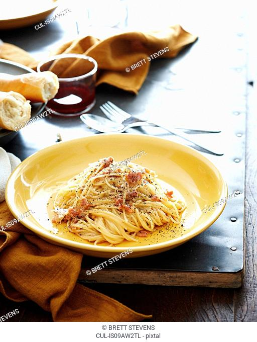 Set table with bowl of spaghetti with pork cheek and seasoning