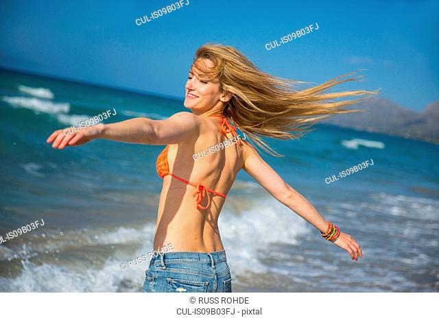 Young woman on beach, arms outstretched, smiling