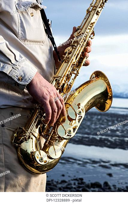 A Man Stands With A Saxophone On The Beach At The Water's Edge; Alaska, United States Of America