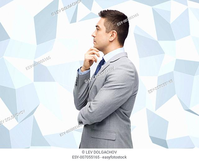 business and people concept - thinking businessman in suit making decision over gray graphic low poly background