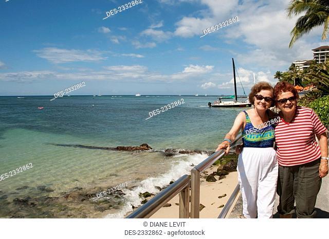 Two sisters posing along the shoreline, Waikiki Beach; Oahu, Hawaii, United States of America