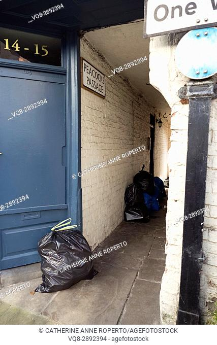 Marine blue door leading to Peacocks Passage ironically full of rubbish sacks and waste, Rochdale, Yorkshire, England, UK