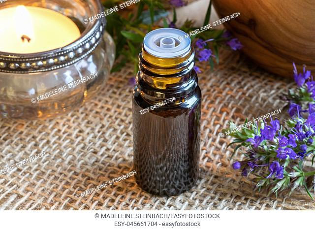 A bottle of essential oil with fresh blooming hyssop twigs and a candle