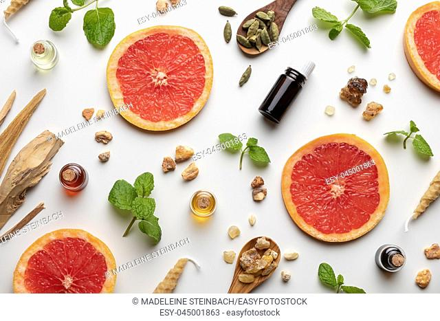 Bottles of essential oil with fresh grapefruit, peppermint, white sandalwood, cardamon and other ingredients