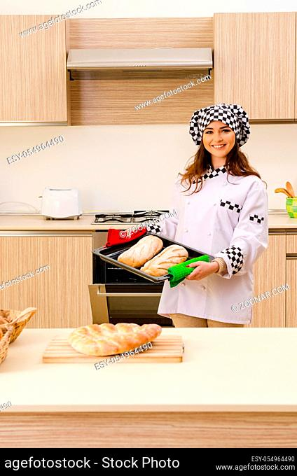 Young female baker working in kitchen