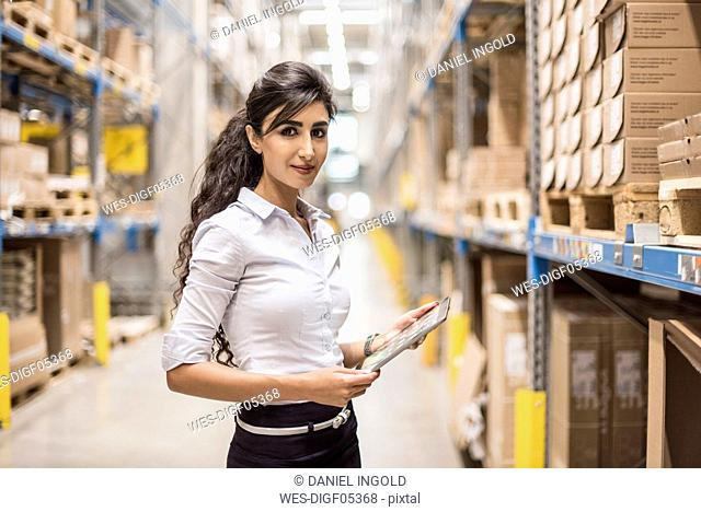 Portrait of confident woman holding tablet in factory storehouse