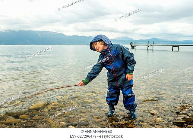 Cute little boy playing by the lake, pretending fishing, wearing blue waterproof all-in-one suit and rain boots