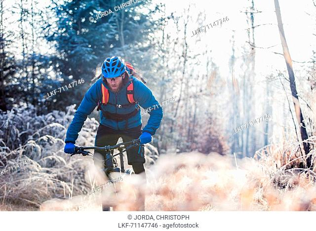 Young man riding with his bike through a with frost covered forest, Allgaeu, Bavaria, Germany