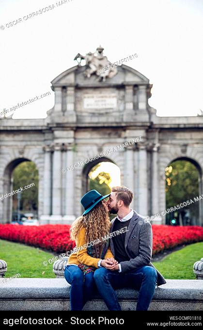 Man and woman kissing while sitting against gate in city