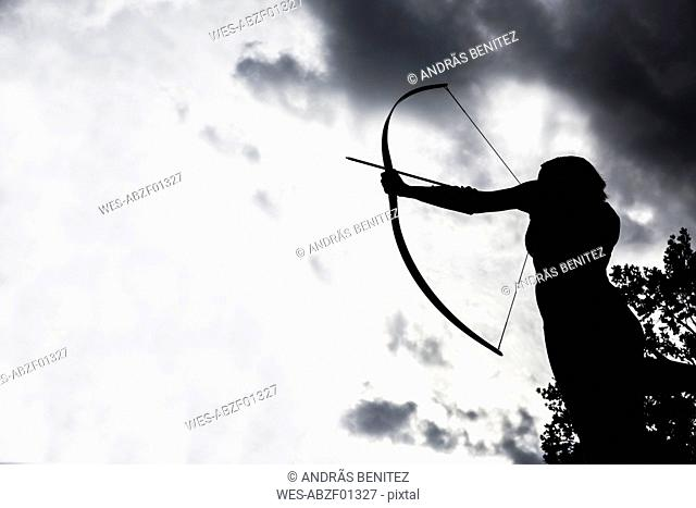 Silhouette of an aiming archeress