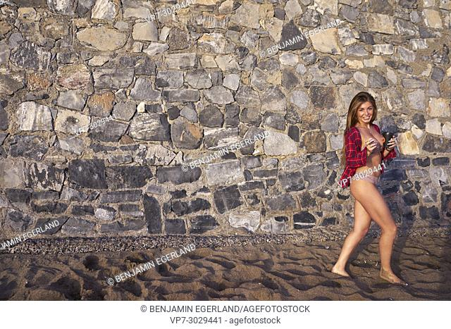 happy girl in bikini walking with caffe cup, at beach against stone wall. Russian ethnicity. In holiday destination Hersonissos, Crete, Greece