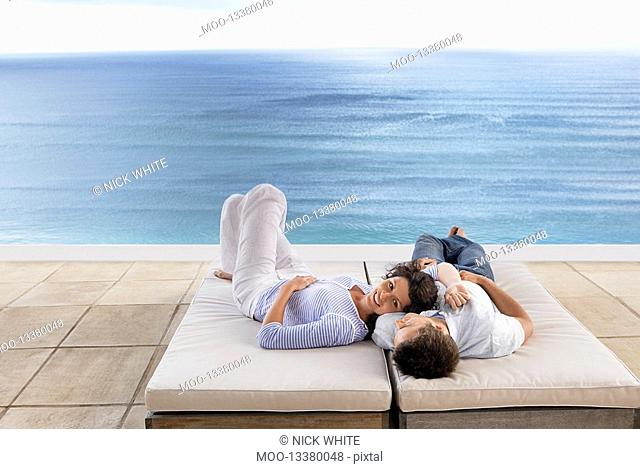Couple lying down on sun beds on terrace overlooking sea elevated view