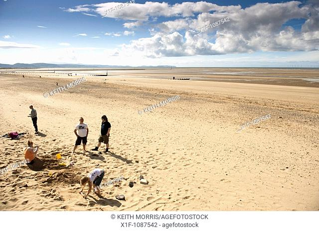 A family on the deserted beach and seaside, Rhyl, north wales UK