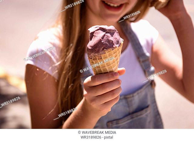 Girl hand holding waffle cone with ice cream on a sunny day