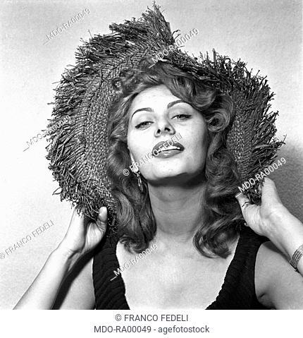 Italian actress Sophia Loren posing with a straw hat. 1957