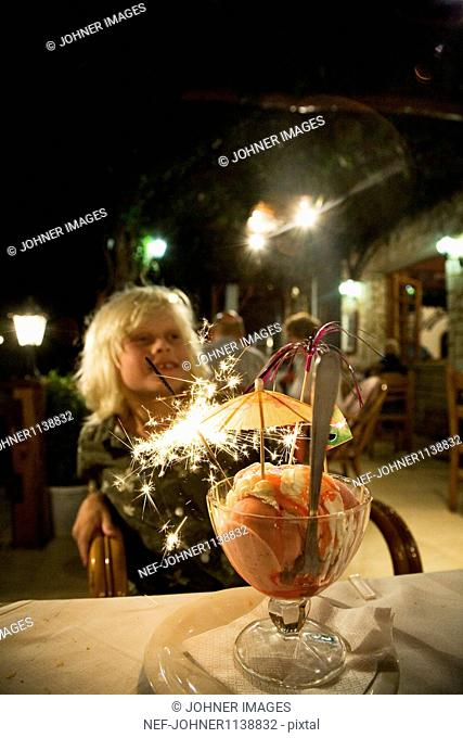 Boy eating ice cream with illuminated sparkler