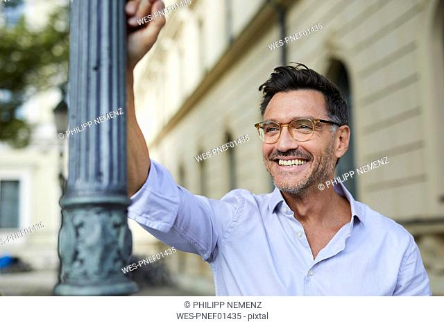 Portrait of happy businessman leaning against lamp post in the city