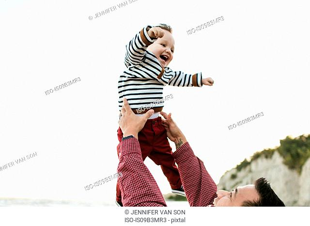 Father throwing smiling baby boy in air