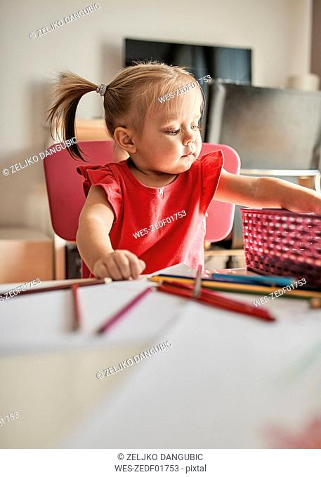Portrait of little girl drawing with coloured pencils