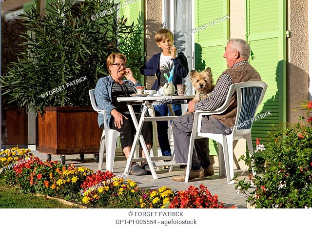 ELDERLY COUPLE WITH THEIR GRANDSON ON THE HOME'S TERRACE, TOWN OF VERNEUIL-SUR-AVRE (27), FRANCE