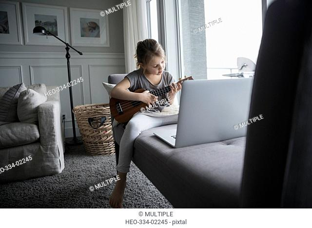 Girl playing ukulele at laptop in living room